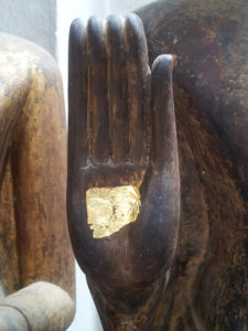 Gold leaf on a Buddha's palm in Laos