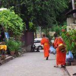 Monks walking down a street