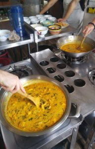 Stirring the laksa curry, one chicken, one vegetarian.