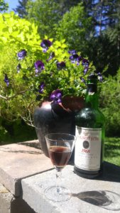 A glass of port, a bottle and violets