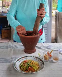 Pounding ingredients for papaya salad