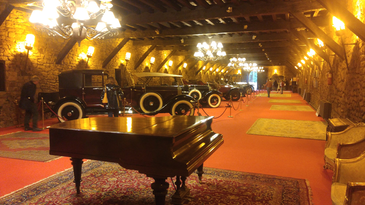 A piano in an elegant hall of antique cars