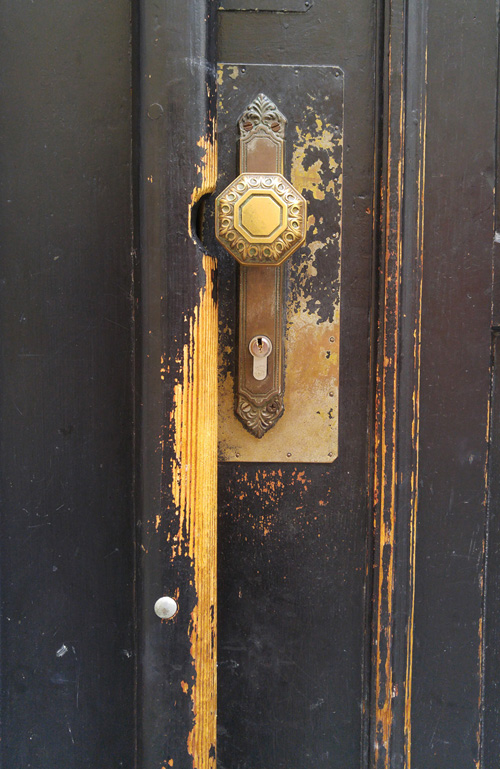 brass door handle on black door