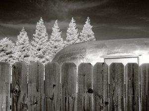 silver trailer behind a wodden fence