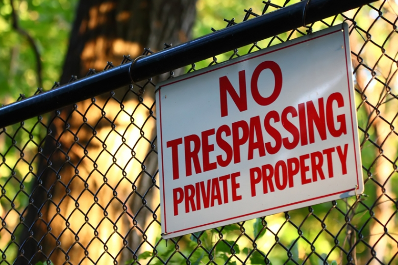 no trespassing sign on chainlink fence